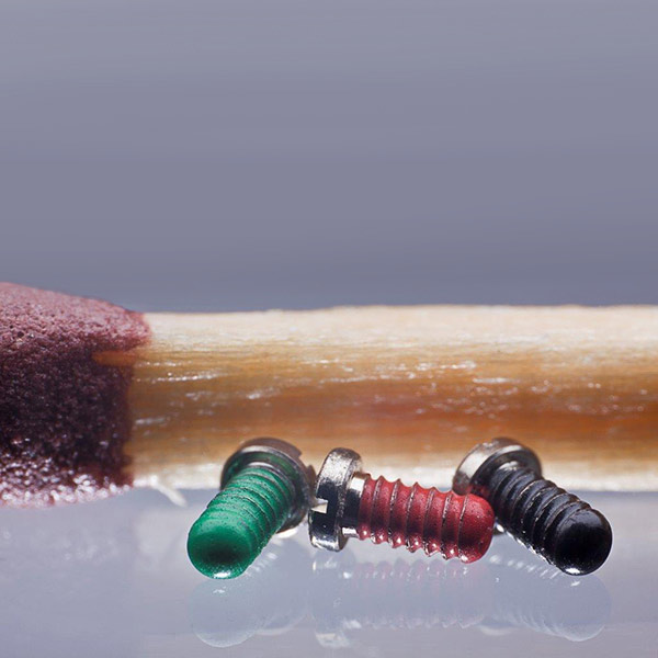 Miniature screws with thread lock coating for the watch industry.